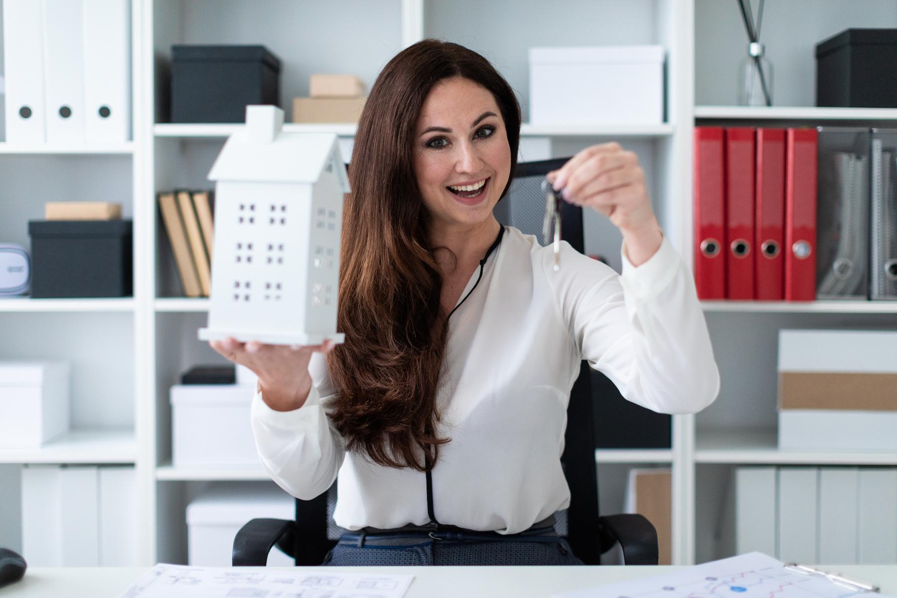 Mulher segurando um modelo de prédio em uma mão e uma chave em outra