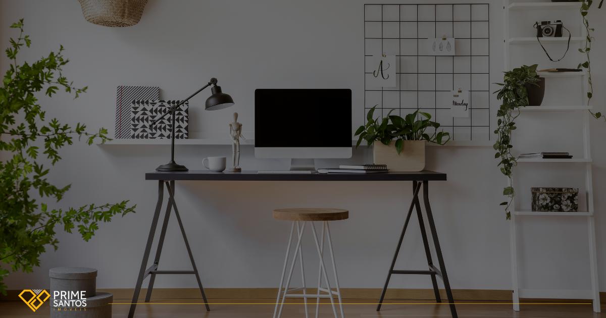 Home office na quarentena: Como equilibrar a vida profissional e pessoal |Na imagem temos uma mesa de home office com computador, um boneco de madeira articulado e uma luminária, ainda temos um banco de madeira, uma estante e o memory borda na parede.
