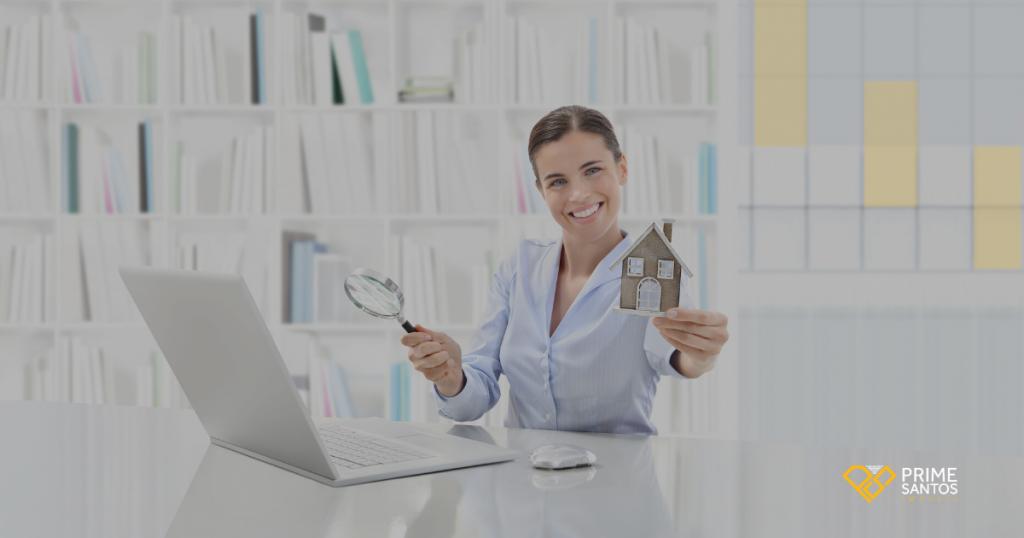 Coronavírus: o que esperar do mercado imobiliário? | Na imagem tem uma mulher sentada a frente do computador com uma lupa analisando o mercado