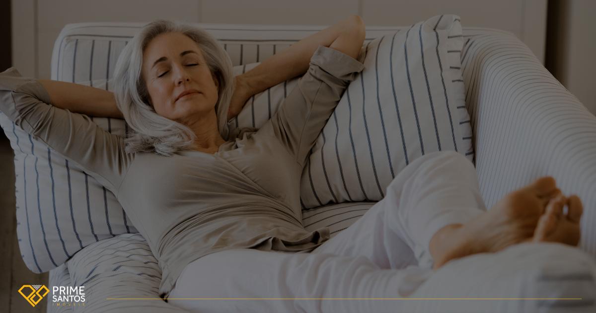 Home office na quarentena: Como equilibrar a vida profissional e pessoal | Na imagem tem uma mulher de meia idade e cabelos grisalhos descansando confortavelmente em seu sofá