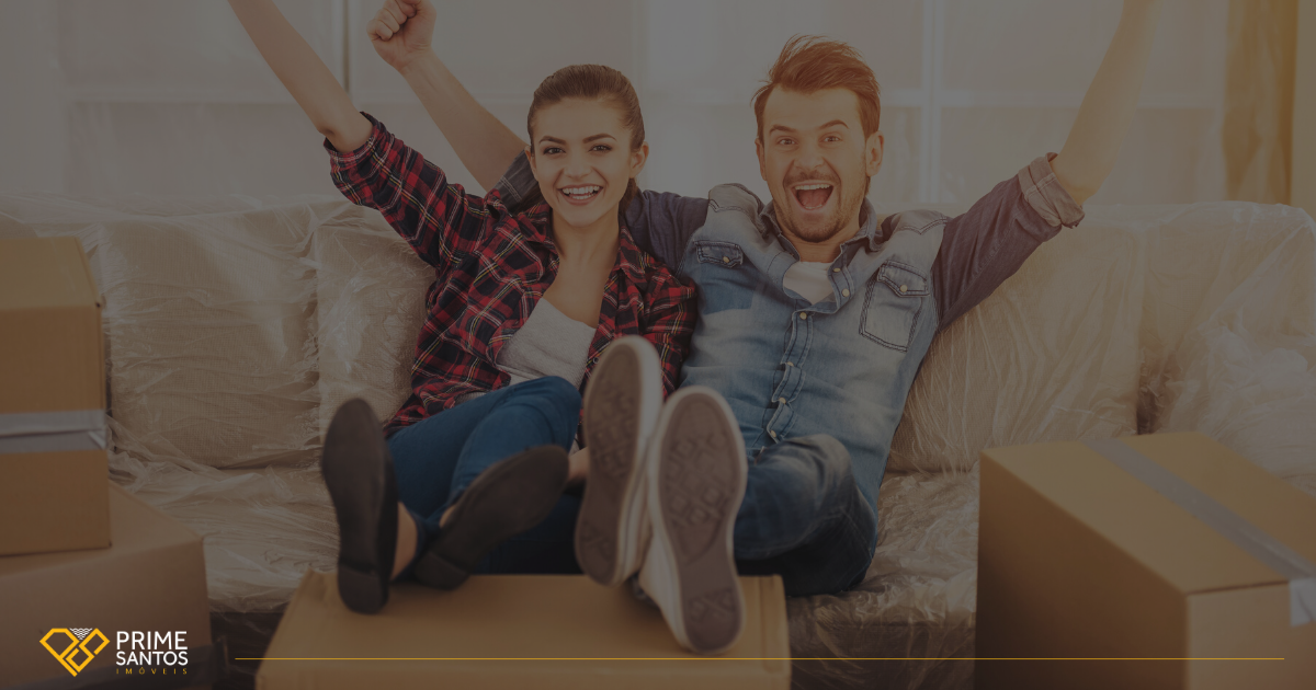 Seu imóvel em Santos, a um clique! | Na imagem tem uma mulher e um homem, formando um casal, sentados no sofá de casa comemorando a mudança cercados de caixas de papelão.